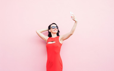 Youth and technology. Attractive young woman in red dress taking selfie .