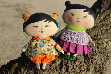 Two textile handmade doll japanese girls with black hear sitting on the tree