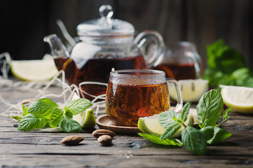 Hot black tea with lemon and mint on the wooden table