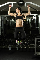 Sexy Brunette fitness bikini girl with perfect shape body making elevations pull up in gym