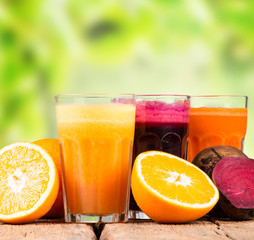 Fresh juices, orange, beetroot and carrot on wooden table