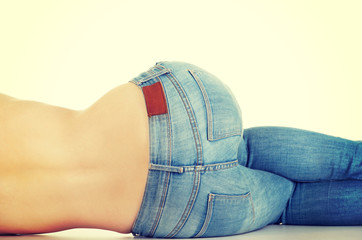 Shirtless woman lying in jeans.
