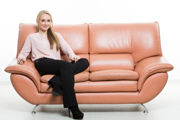 Elegant beautiful woman sitting on a couch a leather. isolated on white. Training managers. sales agents. non-verbal communication. one leg curled under itself