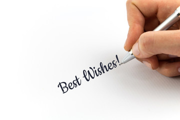 "Hand writing ""Best Wishes!""  on white sheet of paper."