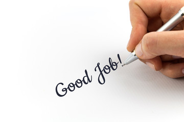 "Hand writing ""Good Job"" on white sheet of paper."