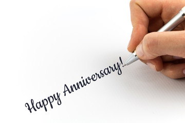 "Hand writing ""Happy Anniversary,!""  on white sheet of paper."