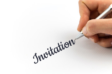 "Hand writing ""Invitation"" on white sheet of paper."