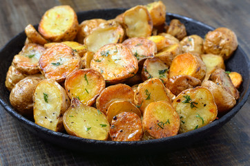Fried potato in pan on wooden table