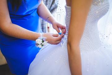 Bridesmaid Tying Bow on Dress
