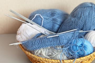 Needlework. Knitting dual elastic band. Balls of wool yarn in a wicker basket