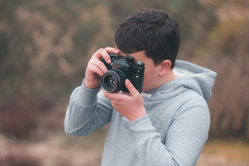 Young boy shooting with vintage camera