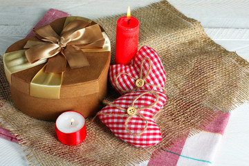 Decorative hearts for Valentine's day with candle and gift on fabric on wooden background