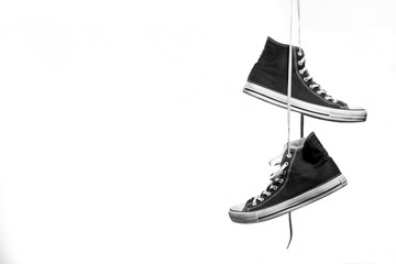 Black and white shot of pair of sneakers hanging in front of a white background