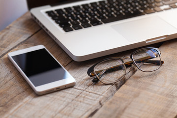 Close up of glasses, smartphone and laptop on a wooden desktop.