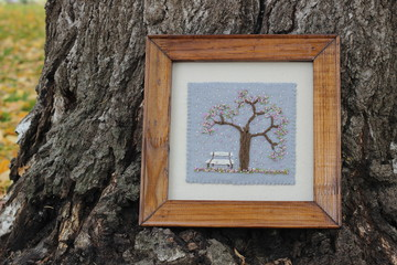 Embroidery picture bench in a garden, a blossoming tree in fallen autumn leaves