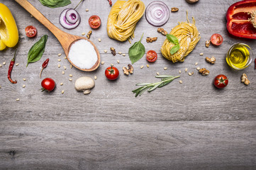Healthy foods, cooking and vegetarian concept pasta with flour, vegetables, oil and herbs on wooden rustic background top view border, place for text