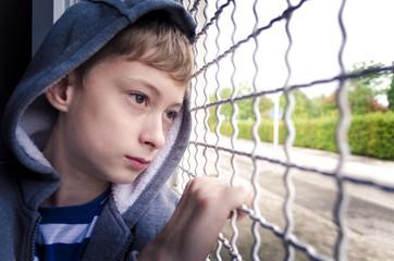 Sad boy closeup behind bars