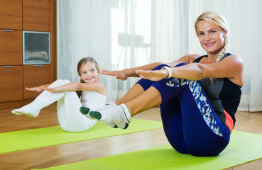 Positive mother and little daughter working out at home