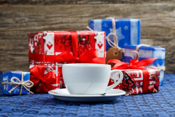Christmas table with cup of tea and gifts.