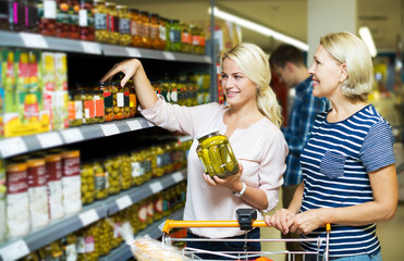 Women standing near shelves with canned goods