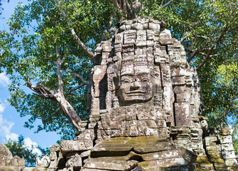Smiling stone face on the ruins of famous Angkor Wat temple in Cambodia