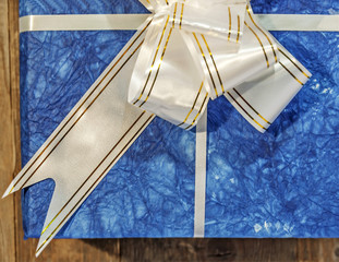 Blue gift box with white and golden ribbon and bow