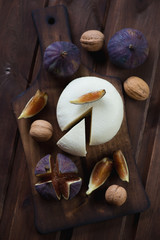 Cheese with figs and walnuts on a dark rustic wooden surface