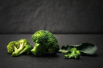 still life with fresh green broccoli on black stone plate
