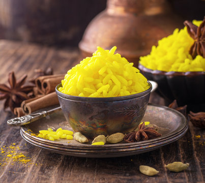 Bright yellow boiled rice with turmeric and aromatic spices on a dark wooden background in old vintage metal bowl