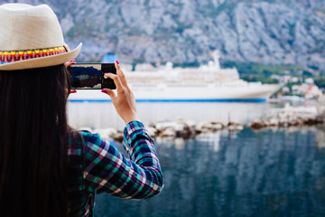 girl taking photo of cruise liner yacht