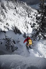 A telemark skier jumping into a narrow chute in Bridger Bowl, Montana.
