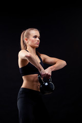 Fitness young woman standing with kettlebells on black background