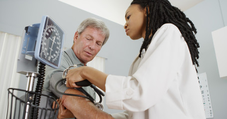 African woman doctor checking patient's blood pressure