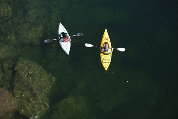 A young adult couple kayaking on a sunny day on Lake Pend Oreille in Sandpoint, Idaho.
