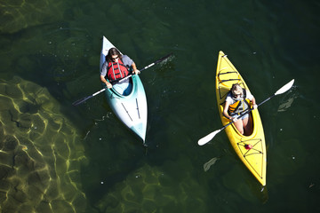 Young couple kayaking together in a lake during sunny day