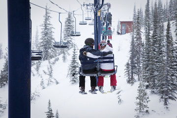 Two young adults smile while sitting on a double chairlift at Schweitzer Mountain in Sandpoint, Idaho.
