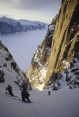 Skiers Kasha Rigby, and Hilaree O'Neill, skiing a steep couloir on Baffin Island, Nunavit territory, Canada.