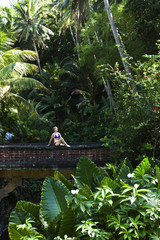 A beautiful woman relaxing on a bridge next to a hot springs surrounded by a lush jungle and flowers in Lovina, Bali, Indonesia.