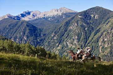 Two cowboys ride their horse through a Colorado alpine field with a mountain backdrop.