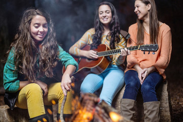 Three young women laugh while playing music and singing around a campfire at Lake Chinnabee.