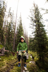 A five year old Japanese-American boy, (a dragon cape, green fleece) sits on the trail sign for Silver Creek (trail number 1141) on a hike toward the lake near Baker Pass.