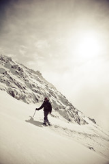 A mountaineer hikes up a snow covered mountain ridge near Chilliwack, BC, Canada in the North Cascade Mountain Range.