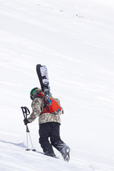 A male skier hikes a ridge on Lone Peak at Big Sky Resort the largest ski resort in the United States by acreage with 5,750 acres, 30 lifts and a vertical drop of 4,350 feet located in Big Sky, Montana.