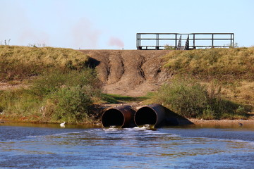 Storm drain pipes emptying water into a coastal estuary