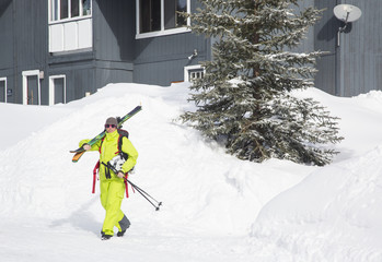 A fit female skier walks out of her condo and carries her skis to ski Big Sky Resort in Big Sky, Montana.