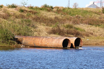 Storm drain pipes emptying water into a coastal estuary viewed from side