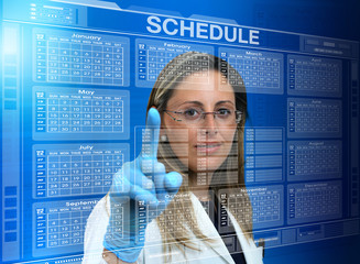 woman doctor using a virtual touch screen interface with a calendar medical / female doctor touching the interface of a virtual application with medical agenda