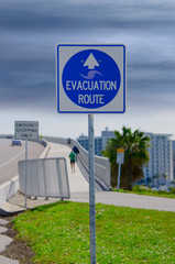 Emergency Evacuation Route sign with looming storm clouds in the background