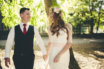 Vintage portrait of a young hipster couple posing  in wedding suite and dress at sunset in the forest