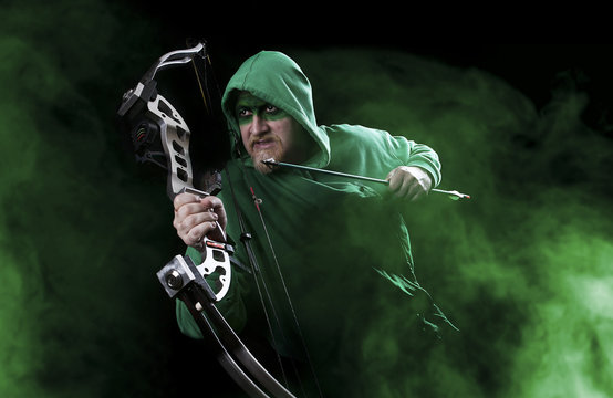 Man in green with mask holding bow and arrow